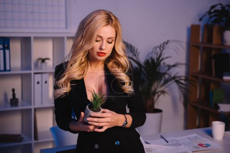 sexy blonde woman looking at artificial plant in office
