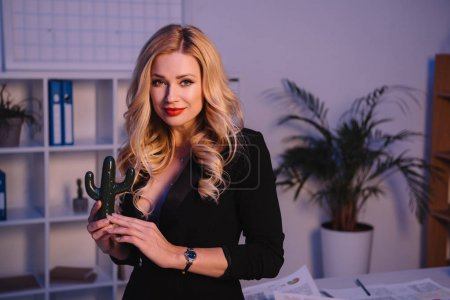 smiling sexy woman holding artificial cactus in office and looking at camera