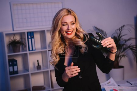 smiling sexy businesswoman holding artificial cactus in office