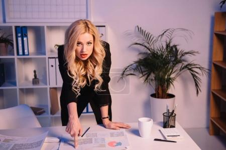angry businesswoman pointing on documents on table and looking at camera