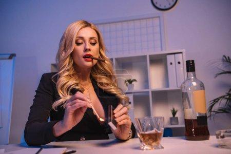 seductive woman lighting cigar with match