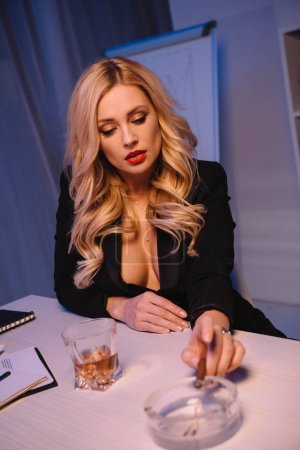beautiful sexy blonde woman holding cigar in hand