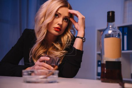 tired blonde businesswoman sitting at table with glass of whiskey