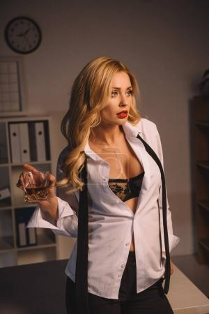 seductive woman posing with glass of whiskey and looking away