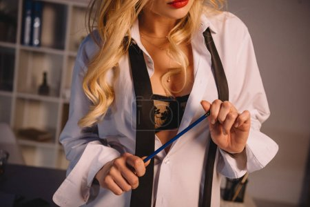 cropped image of sexy woman in unbuttoned shirt and black bra holding pencil