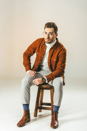 stylish man looking at camera while sitting on wooden chair, on beige