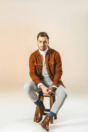 fashionable man in eyeglasses looking at camera sitting on wooden chair, on beige