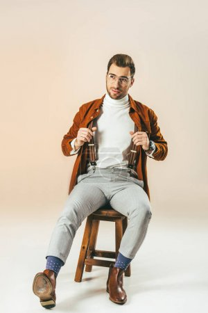 handsome pensive man looking away while sitting on wooden chair, on beige