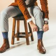 Cropped shot of stylish man tying socks while sitting on wooden chair, on beige