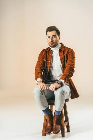 Photo pour Songeur jeune homme en vêtements à la mode, assis sur une chaise en bois, sur beige - image libre de droit
