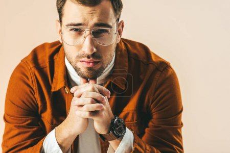 portrait of thoughtful stylish man with hands in lock looking at camera isolated on beige