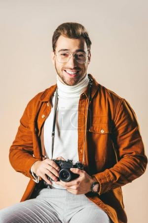 portrait of cheerful man in stylish clothing with photo camera looking at camera isolated on beige