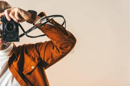 Photo pour Vue partielle de l'homme qui prenait la photo sur appareil photo isolé sur beige - image libre de droit