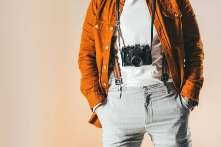 partial view of man in fashionable clothing with photo camera isolated on beige