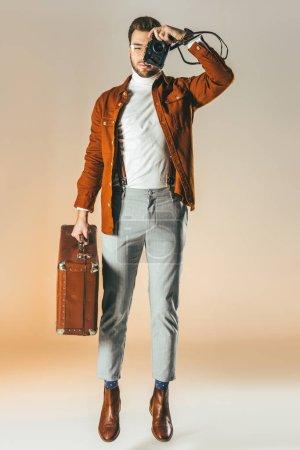 Photo pour Chic homme sautant avec valise en main prendre photo sur appareil photo - image libre de droit
