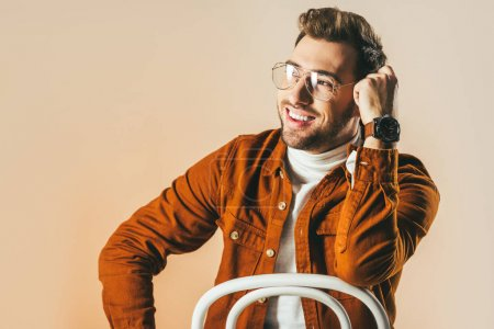 portrait of happy man in fashionable clothing and eyeglasses looking away isolated on beige