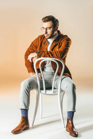 thoughtful man in fashionable clothes resting on chair