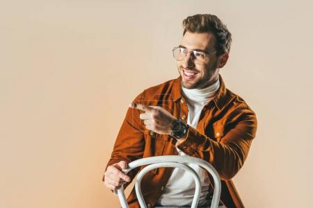 portrait of cheerful fashionable man pointing away isolated on beige