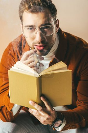 portrait of young man with cigar and book in hands looking at camera isolated on beige