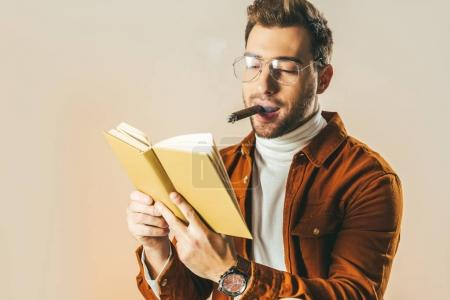 portrait of young man with cigar reading book isolated on beige