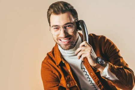 portrait of cheerful man talking on telephone isolated on beige
