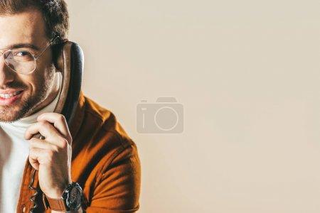 Photo pour Vue partielle de l'homme souriant talking téléphone isolé sur beige - image libre de droit