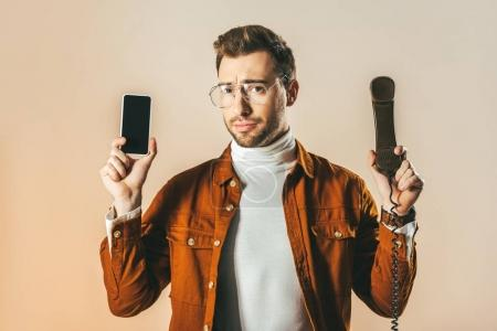 portrait of handsome man showing smartphone and telephone tube in hands isolated on beige