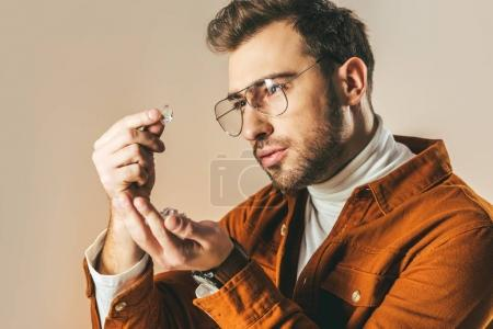 side view of fashionable man looking at diamond in hand isolated on beige