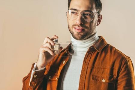 Photo pour Portrait de l'élégant jeune homme appliquant parfum isolé sur beige - image libre de droit