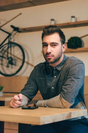 portrait of pensive man looking at camera while sitting at table with smartphone in cafe
