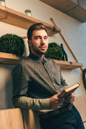 portrait of stylish man with book in hands looking away in cafe