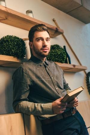 Photo pour Portrait d'un homme élégant avec livre en mains regardant loin dans café - image libre de droit