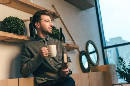 Photo for Portrait of smiling man with cup of coffee and book in hands in cafe - Royalty Free Image