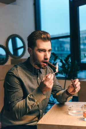 portrait of young man lighting up cigar while sitting at table in cafe