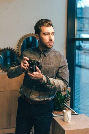 Foto de Retrato de hombre pensativo con foto cámara de pie en la ventana en la cafetería - Imagen libre de derechos