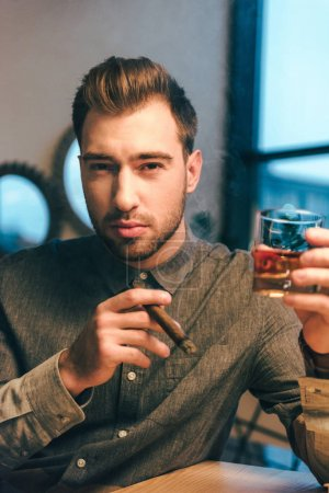 portrait of young man with glass of cognac and cigar in hands in cafe