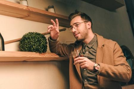 side view of fashionable man with glass of whiskey waving to someone in cafe