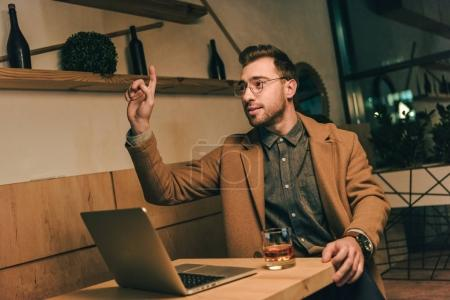 portrait of young man at table with laptop calling for waiter in cafe