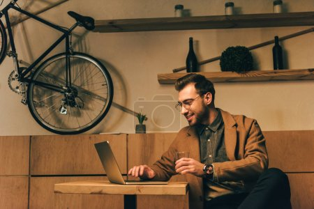 portrait of smiling man with glass of whisky using laptop at table in cafe