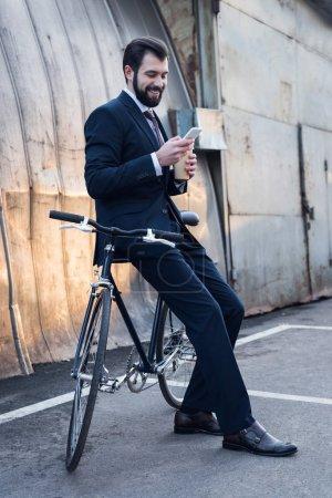 Photo pour Homme d'affaires souriant avec café pour aller à l'aide d'un smartphone tout en s'appuyant sur le vélo sur la rue - image libre de droit