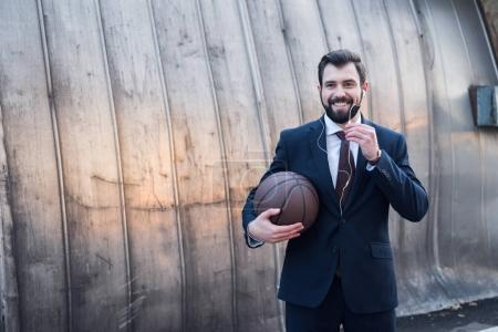 portrait of smiling businessman in earphones with basketball ball on street