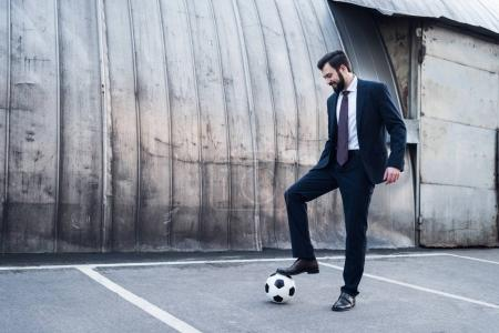 smiling businessman in suit playing soccer on street