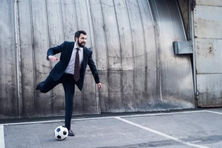 young smiling businessman in suit playing soccer on street