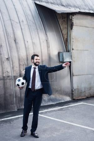 young smiling businessman in suit pointing away while playing soccer on street