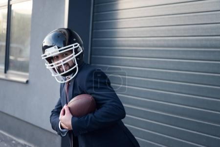 young businessman in suit and rugby helmet with ball in hands standing on street