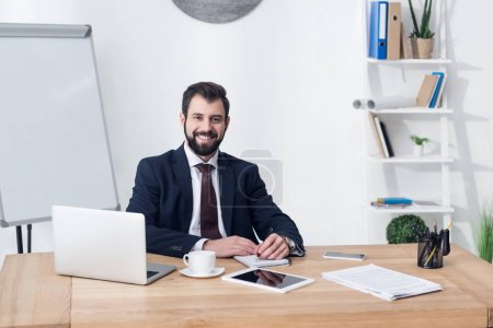 portrait of smiling businessman looking at camera while sitting at workplace in office