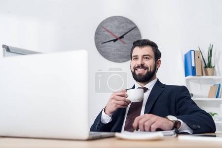 Photo pour Mise au point sélective de gai homme d'affaires en costume buvant un café dans le milieu de travail au bureau - image libre de droit