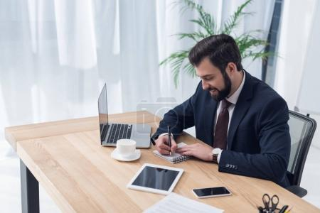 side view of businessman making notes in notebook at workplace in office
