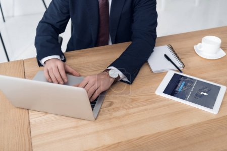 Partial view of businessman working on laptop at workplace with tablet with tumblr app in office