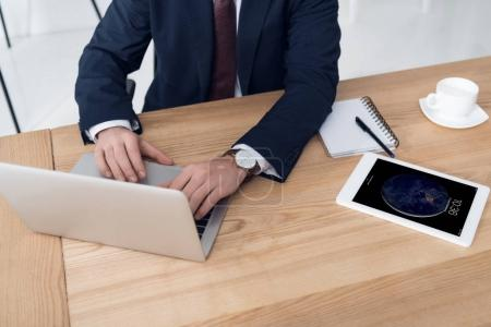 partial view of businessman working on laptop at workplace with tablet in office